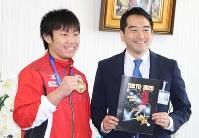 五十嵐立青つくば市長(右)を表敬訪問し、ワールドカップの金メダルを披露する宮地秀享選手=つくば市研究学園1で