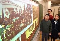カラー化された集合写真(画面手前)と元の写真(画面奥)を見つめる(左から)浜井さん、渡邉准教授、庭田さん=広島市中区の広島女学院高で