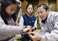 延年祭のタチバナの作り方を教わる子どもたち。浦嶋神社の伝統は貴重な学びのフィールドだ=京都府伊根町本庄上の集会所で、安部拓輝撮影