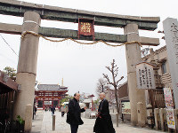 四天王寺の西側にある石の鳥居前で話す高島幸次さん(左)と瀧藤康教さん。「天王寺詣り」では、ここから境内の案内が始まる。奥に見えるのが極楽門と五重塔=大阪市天王寺区で、山田夢留撮影