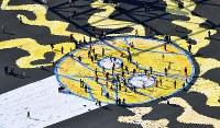 東日本大震災の被災者らが夢をつづったハンカチを使って巨大アートを描く参加者たち=大阪府吹田市で2018年3月17日、本社ヘリから貝塚太一撮影