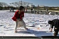 東日本大震災の被災者らが夢をつづったハンカチを使って巨大アートを描く参加者たち=大阪府吹田市で2018年3月17日、幾島健太郎撮影