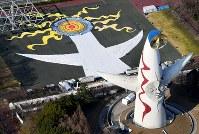 東日本大震災の被災者らが夢をつづったハンカチを使って描き出された巨大アート。右下は太陽の塔=大阪府吹田市で2018年3月17日、本社ヘリから貝塚太一撮影