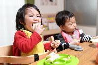 料理を直接、手で食べる「手づかみ食べ」をする1歳の女の子。まだ歯も生えそろっていないが、もぐもぐとおいしそう=兵庫県尼崎市で、大西岳彦撮影