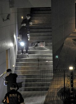 Police investigate an area near the entrance of an apartment building where a woman was found collapsed and bleeding, in the Tokyo suburban city of Tama on March 16, 2018. (Mainichi)