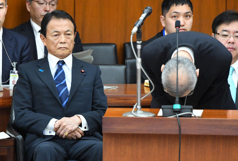 Financial Bureau chief Mitsuru Ota, right, bows in apology over the land sale document scandal during a House of Representatives Financial Affairs Committee meeting, on March 16, 2018, as Finance Minister Taro Aso looks on. (Mainichi)