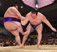 Yokozuna Kakuryu, right, pushes Takakeisho out of the ring at Edion Arena Osaka on March 17, 2018. (Mainichi)