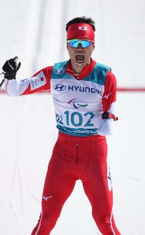 Japan's Yoshihiro Nitta finishes his race in first place in the standing category of the cross-country 10-kilometer classical skiing of the Pyeongchang Paralympics at Alpensia Biathlon Centre on March 17, 2018. (Mainichi)