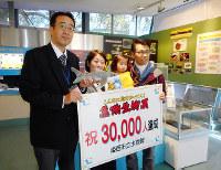 危険生物展の入場者が3万人を突破し、3万人目の家族にサメのぬいぐるみが贈られた=兵庫県姫路市西延末の市立水族館で、田畑知之撮影