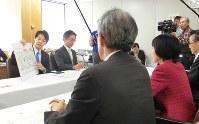 高橋知事(手前右)にバス転換について説明する夕張市の鈴木市長(同左)=夕張市役所で