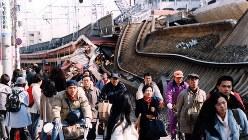 阪神大震災で崩壊した阪急電鉄線路の横を、生活用品を求めて歩く人たち=兵庫県西宮市で1995年1月20日