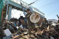 A U.S. Marine assists Japanese Self-Defense Force members in removing debris from the grounds of Minato Elementary School in Ishinomaki, Miyagi Prefecture, in this file photo taken on April 1, 2011. (Mainichi)