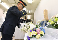 A Tokyo Metro Co. senior manager lays flowers on a commemorative stand at Kasumigaseki Station, where the sarin nerve gas attack occurred in 1995, in Tokyo's Chiyoda Ward, on March 20, 2018. (Pool photo)