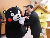 直筆のお礼の色紙を手渡したくまモン(左)=島根県庁で、前田葵撮影