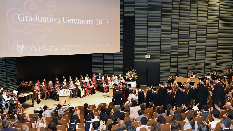 講堂に入場する修了生を拍手で迎える聴衆=写真はすべてOIST提供