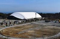 一部再開に向け復旧工事が進むJヴィレッジ。後方は新設の全天候型練習場=楢葉町山田岡で