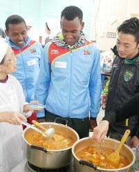郷土料理「アリチャ」を見つめるエリトリアからの留学生(左から2人目と3人目)=大磯町で
