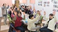 「100歳目指して人生バンザイ」と手を上げる認知症カフェの参加者=福岡県大牟田市で2018年2月1日
