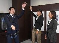 セーリングで使う用具を身につけるスポーツ庁の鈴木大地長官(左)と、競技中のフォームを伝える吉岡美帆(中央)と吉田愛