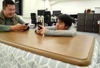 オフィスのこたつでスマートフォンを触りながらアイデアを練るワンファイナンシャルの山内奏人CEO=東京都港区の同社で2018年2月、岡大介撮影
