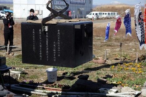 移設するためつり上げられる閖上中学校跡地の慰霊碑=宮城県名取市で2018年3月24日午前9時9分、喜屋武真之介撮影
