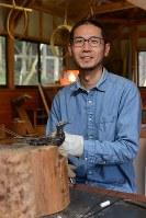 山あいの集落の工房で作品を作る篠原さん。最近では鉄を使った作品作りにも挑戦=大分県日田市の工房で
