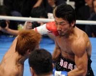 一回、湯場忠志(左)の左フックで1回目のダウンを奪われる牛若丸あきべぇ=東京・後楽園ホールで2007年12月6日、丸山博撮影