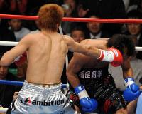 【ボクシング日本ウエルター級タイトルマッチ】一回、湯場忠志(手前)の左フックでふらついた後、止めの右ストレートを浴びる牛若丸あきべぇ=東京・後楽園ホールで2007年12月6日、丸山博撮影