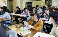 この日の勉強のテーマは「放射線物理学入門」。ルビ入りの資料を見ながら「むずかしいわ~」=神戸市長田区の市立長田公民館で、木田智佳子撮影