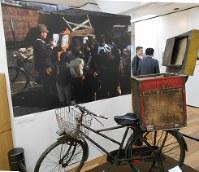 敗戦後の日本を撮影した写真を展示する「希望を追いかけて」展。写真は紙芝居を見る子どもたち=東京都千代田区の昭和館で2018年3月9日、栗原俊雄撮影