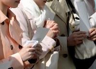 合格発表を待つ間、お守りを握りしめる受験生=兵庫県宝塚市で2018年3月29日、平川義之撮影