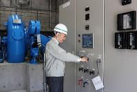 発電スイッチを入れる姫路土木事務所関係者=兵庫県朝来市生野町の生野ダムで、中治愛美撮影