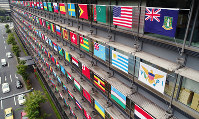 Flags of the 206 International Olympic Committee member nations and regions are seen displayed on the facade of the Palaceside Building, home to The Mainichi Newspapers Co. headquarters, in Tokyo's Chiyoda Ward on Oct. 28, 2017. (Mainichi)