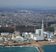 In this March 4, 2017 file photo, Japan Atomic Power Co.'s idled Tokai No. 2 nuclear power station is seen at right, in Tokai, Ibaraki Prefecture. (Mainichi)