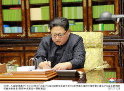 大陸間弾道ミサイル(ICBM)「火星15」型の試射を承認するために署名する金正恩・朝鮮労働党委員長=朝鮮中央通信・朝鮮通信