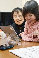 オリヒメをタブレット端末で操作しながら終業式に臨む加藤愛美さん(右)=鳥取県米子市で、小野まなみ撮影