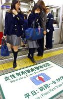 新しく導入された女性専用車両を利用する学生ら=大阪市営地下鉄御堂筋線なんば駅で2002年11月11日、佐藤賢二郎撮影
