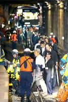 地震発生と大津波警報の発令を想定した大阪市営地下鉄での避難訓練で、車両から最寄りの駅のホームまで線路上を誘導される人たち=大阪市住之江区で2013年10月19日午前1時26分、後藤由耶撮影