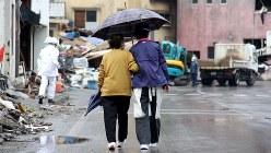 小雨の中、港周辺の被災地を寄り添いながら歩く人たち。住民相互の心のつながりがここでは生きている=岩手県釜石市で2011年5月28日