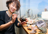 趣味で収集する鉱石をルーペで見つめる小説家の堂垣園江さん=大阪市北区で、貝塚太一撮影