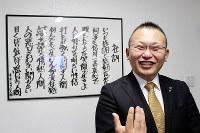 上森秀夫さんの笑顔は代名詞。直筆の社訓を前に=滋賀県湖南市岩根のインフィニティ会議室で、大澤重人撮影
