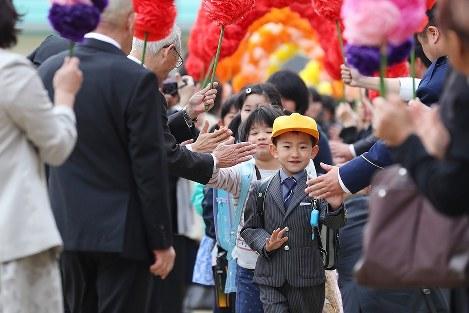 再開式前に村民手作りの「花のトンネル」で出迎えられる葛尾村立小・中学校の児童生徒たち=福島県葛尾村で2018年4月6日午前、喜屋武真之介撮影