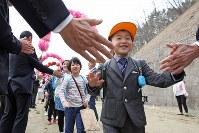 開校式前に村民手作りの「花のトンネル」で出迎えられる葛尾村立小・中学校の児童生徒たち=福島県葛尾村で2018年4月6日午前9時28分、喜屋武真之介撮影