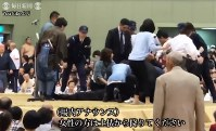 This screen grab from a YouTube video shows women trying to resuscitate the collapsed mayor in a sumo ring in Maizuru, Kyoto Prefecture, on April 4, 2018.