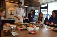 Participants are seen at a sushi-making class at