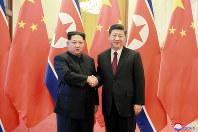 習近平国家主席(右)と握手して記念撮影する金正恩朝鮮労働党委員長=北京の人民大会堂で2018年3月26日、朝鮮中央通信・朝鮮通信