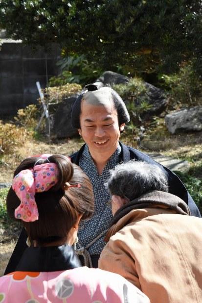 「元気そうじゃねえですかい」。ちょんまげ姿でお年寄りに話しかける新村浩明さん(中央)=福島県いわき市で2018年2月8日、栗田慎一撮影