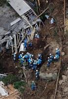 山が崩落し、民家が巻き込まれた現場で救助活動する消防隊員ら=大分県中津市耶馬渓町で2018年4月11日午前10時47分、本社ヘリから