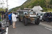 多くの報道陣の間を通って土砂崩れ現場へ向かう自衛隊車両=大分県中津市耶馬溪町で2018年4月11日午前9時59分、矢頭智剛撮影