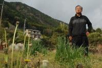 自宅があった土地にたたずむ立野さん。裏山には土砂崩れの痕跡が残ったままだ=熊本県南阿蘇村で2018年4月9日、中里顕撮影